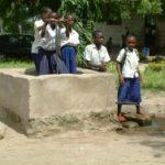 Kinder stehen im Wasserbrunnen